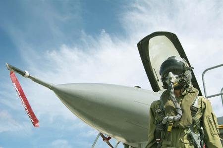 Photo pour Pilot with military suit and military aircraft - image libre de droit