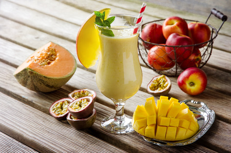 Photo pour Healthy vitamin tropical mango, melon and passion fruit smoothie with yogurt on old wooden background, milkshake - image libre de droit