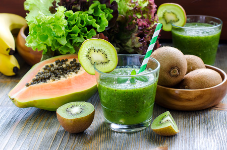 Photo for Green healthy kiwi tropical fruits smoothie with papaya and bananas - Royalty Free Image