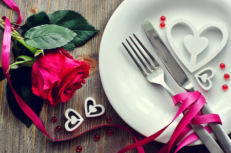 Photo pour Romantic dinner with rose, tableware and hearts on wooden background - image libre de droit