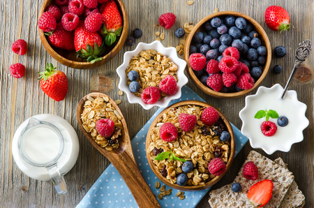 Foto de Healthy breakfast, muesli, raspberries, blueberries, strawberries, crisp bread and yogurt, health and diet concept - Imagen libre de derechos