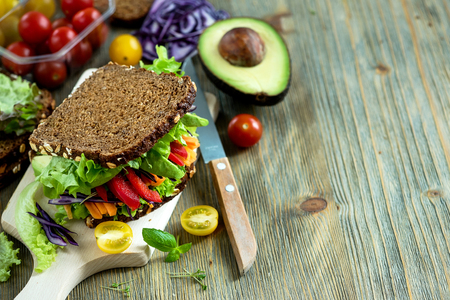 Foto de Vegan rye sandwich with fresh ingredients: avocado, salad, tomato, carrots, for healthy meal, vitamin and diet food copy space - Imagen libre de derechos