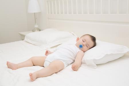Foto de Adorable baby sleeping relaxed and sprawl in parent's bed - Imagen libre de derechos