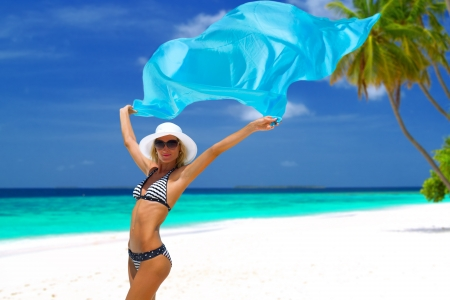 Beautiful bikini model with blue scarf posing on white sandy beach with palm trees and turquoise water on Maldives