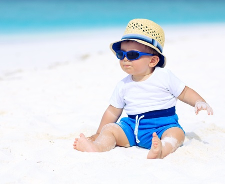 Photo for Baby with hat and sunglasses sitting on the tropical beach - Royalty Free Image