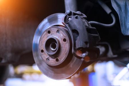 Foto de Car brake disk and caliper close up without wheel in cold colors with beautiful backlight - Imagen libre de derechos