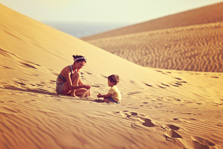 Fit mother with son playing with sand at the desert in Gran Canaria, Maspalomas on sunset