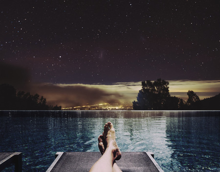 Photo pour Relaxing in holidays, a man feet on bed at swimming pool at night with city lights and stars on sky background - image libre de droit