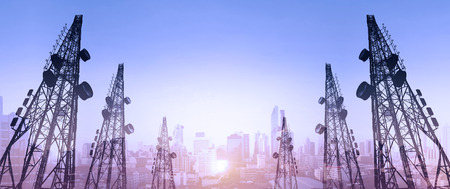 Photo pour Silhouette, telecommunication towers with TV antennas and satellite dish in sunset, with double exposure city in sunrise background - image libre de droit