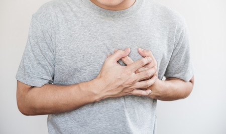 Foto per a man touching his heart. Heart attack, and others heart disease concept, on white background - Immagine Royalty Free