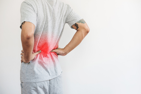 Foto de a man touching his back, with red highlight. Back pain, backache and waist pain, on white background with copy space - Imagen libre de derechos