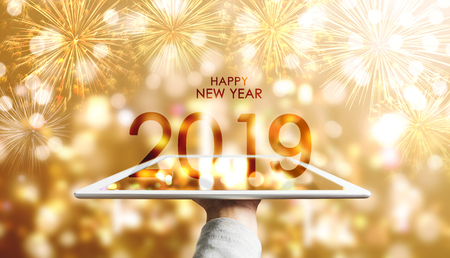 Photo for Happy New Year 2019, Hand holding digital tablet with luxury gold Bokeh fireworks background - Royalty Free Image