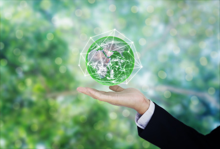 Photo pour Green and environmental global business. Businessman hand holding globe with green Bokeh background. - image libre de droit