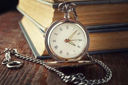 Foto de vintage watch on a chain on a background of old books. Toned photo in a dark key - Imagen libre de derechos