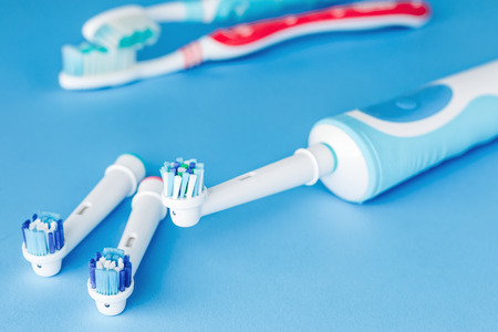Foto de Electric and manual toothbrush  on blue background, close up - Imagen libre de derechos