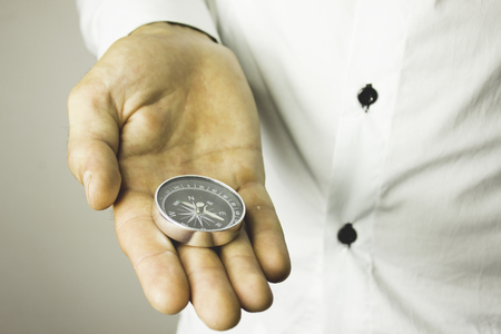 Businessman with a compass holding in hand