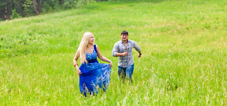Young man and woman running on countryside meadow with green grass