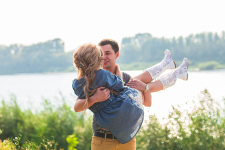 Photo for Man holding woman in his arms on the beach of the river on a sunny day - Royalty Free Image