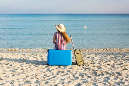 Photo pour Beach, Holiday, Vacation and Happiness Concept - young woman near the sea with her luggage, rear view - image libre de droit
