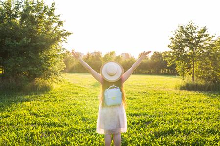Foto de Free happy young woman raising arms watching the sun in the background at sunrise - Imagen libre de derechos