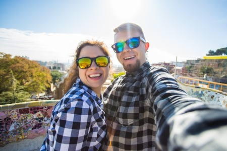 Foto de Travel couple happy making selfie portrait with smartphone in Park Guell, Barcelona, Spain. Beautiful young couple looking at camera taking photo with smart phone smiling in love - Imagen libre de derechos