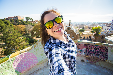Foto de Young happy woman making selfie portrait with smartphone in Park Guell, Barcelona, Spain. Beautiful girl looking at camera taking photo with smart phone smiling - Imagen libre de derechos