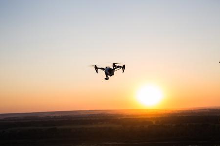 Foto de silhouette of drone, quadrocopter with photo camera flying in the sky. - Imagen libre de derechos