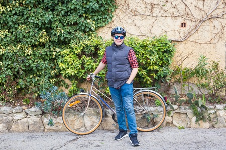 Man in helmet and glasses stay on the bicycle in the garden