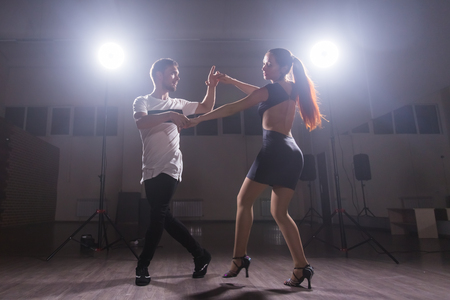 Foto de Active happy adults dancing bachata together in dance class - Imagen libre de derechos