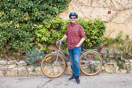 Man in helmet and glasses stay on the bicycle background garden
