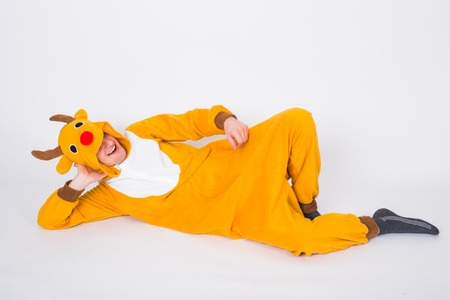 Photo pour Holiday, Christmas and people concept - Man in reindeer costume lying on the white floor - image libre de droit