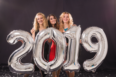 Photo for New Year party concept. Group of young women holding silver colored numbers 2019 and throwing confetti - Royalty Free Image