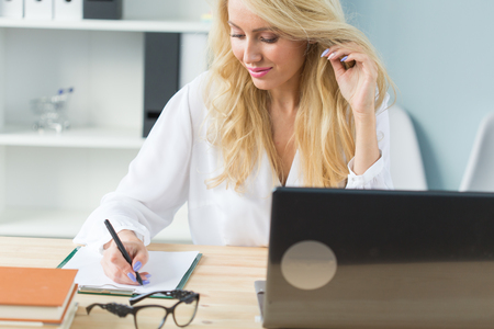 Photo pour Technology, work and people concept - Beautiful blond woman sitting at her desk and making notes in a notebook. - image libre de droit