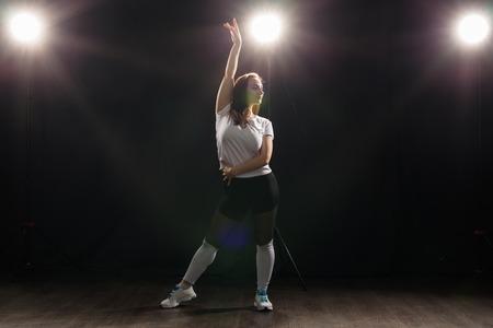 Photo pour Hip-hop, jazz-funk, tecktonik, waacking, trance and street dances concept - Pretty woman dancing jazz funk over dark background - image libre de droit