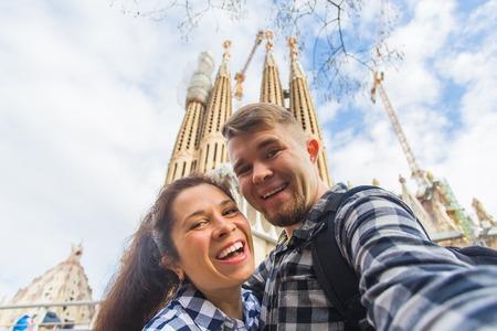 Foto de BARCELONA, SPAIN - FEBRUARY 6, 2018: Happy couple making selfie photo in front of the famous Sagrada Familia catholic cathedral. Travel in Barcelona - Imagen libre de derechos