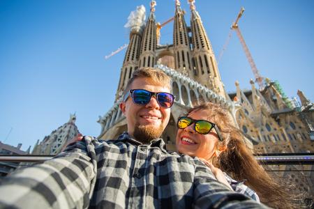 Foto de BARCELONA, SPAIN - FEBRUARY 7, 2018: Happy tourists photographing in front of the famous Sagrada Familia roman catholic church in Barcelona, architect Antoni Gaudi - Imagen libre de derechos