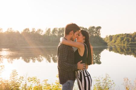 Photo pour Love, romantic and nature concept - young couple hugging near the lake - image libre de droit