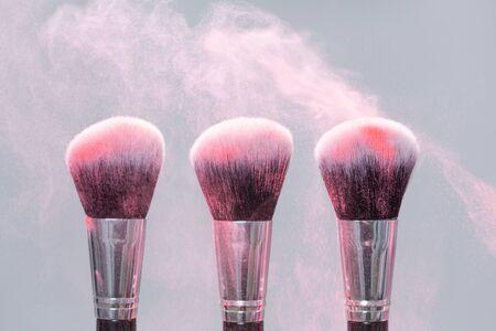 Photo for Make-up brush with pink powder splashes explosion on light background - Royalty Free Image