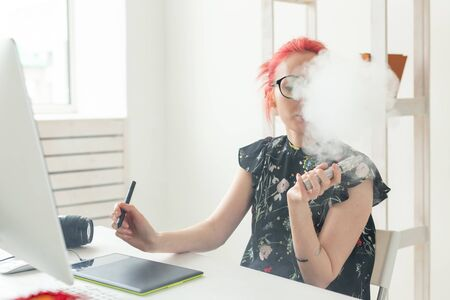 Foto für graphic designer concept - Female graphic designer working on computer while using graphic tablet at desk in the office and smoking a vape - Lizenzfreies Bild