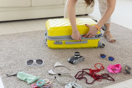 Photo for Vacation, travel and holidays concept - Woman trying to close suitcase with a lot of things. - Royalty Free Image