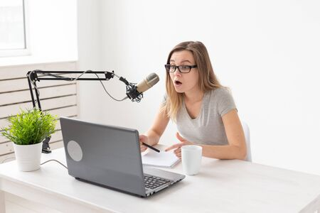 Photo pour Radio, dj, blogger and people concept - young woman presenter working on the radio studio and talking on the microphone - image libre de droit