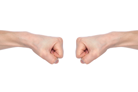 Foto de Two male fists hitting each other, isolated on white background. The concept of business success and teamwork. Close-up - Imagen libre de derechos