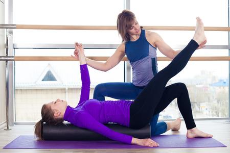 Photo pour Aerobics Pilates personal trainer helping women group in a gym class - image libre de droit