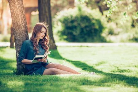 Photo pour Girl reading a book in park, woman, green - image libre de droit