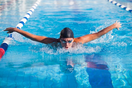 Butterfly swimmer in cap and glasses in the pool