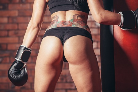 Young sexy girl with boxing gloves. punching bag on the background wall of red brick.