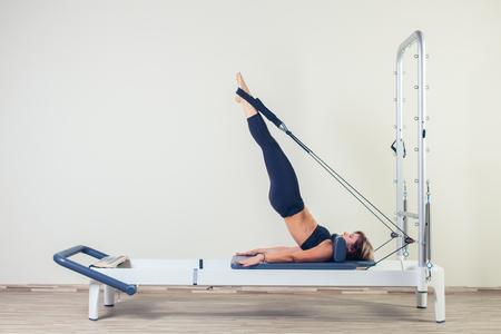 Photo pour Pilates reformer workout exercises woman brunette at gym indoor. - image libre de droit