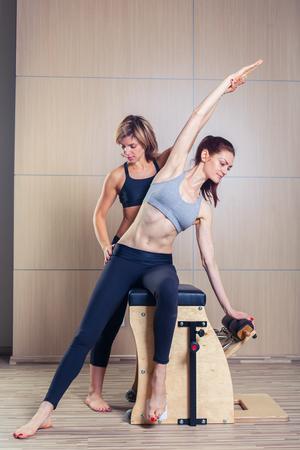 Photo pour combo wunda pilates chair woman with instructor fitness yoga gym exercise - image libre de droit