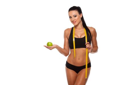 Foto de Sporty woman waist with measure tape and green apple isolated on white. - Imagen libre de derechos