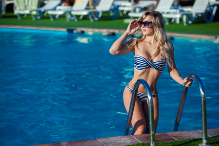 Photo for Beautiful young woman in a pretty swimsuit is standing on a stairs in the swimming pool. She is smiling so wonderful. - Royalty Free Image